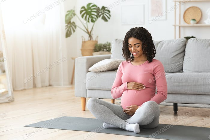 Happy pregnant woman hugging her tummy at home