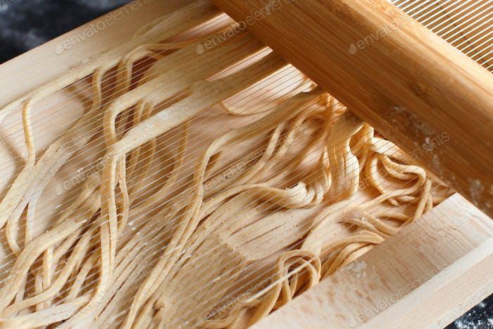 Herstellung von Spaghetti alla chitarra mit einem Werkzeug