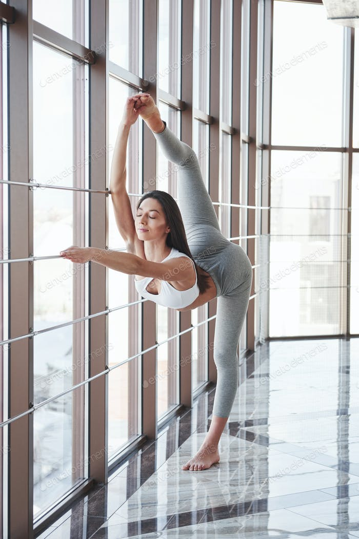 Warming up and doing stretches near the window with handrails at the gym
