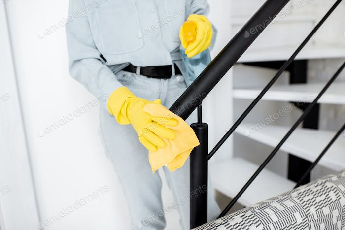 Woman cleaning stair railings at home