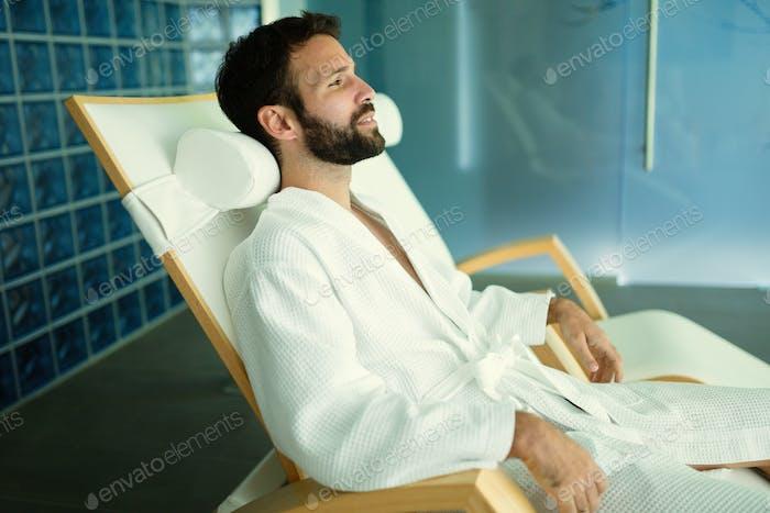 Handsome man relaxing in wellness center