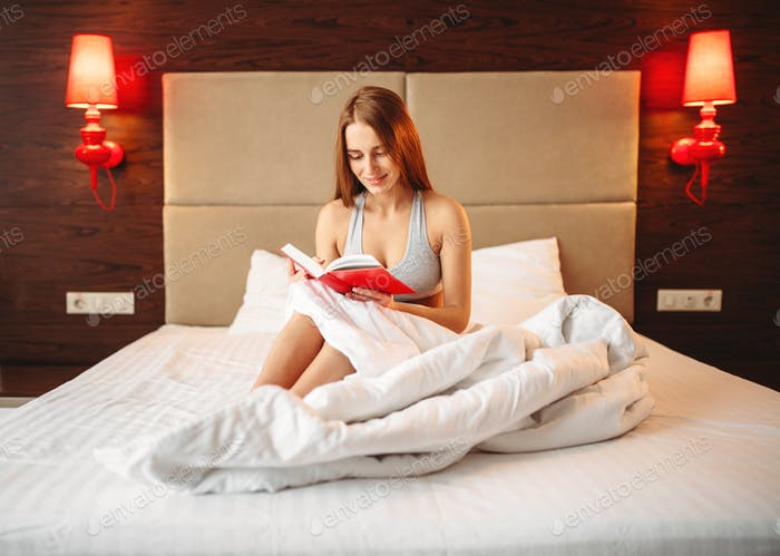 Beautiful woman in underwear reads the book in bed