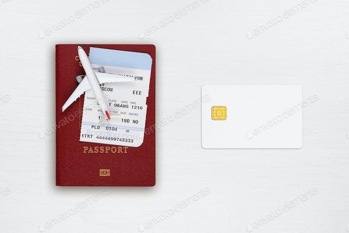 Reisepass, Bordkarte, Spielzeugflugzeug und Kreditkarte auf der Tischplatte