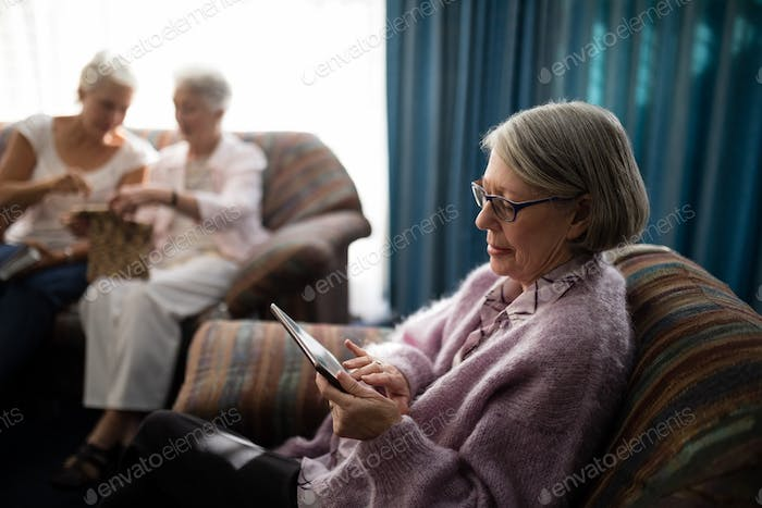 Senior woman using digital tablet while sitting on armchair
