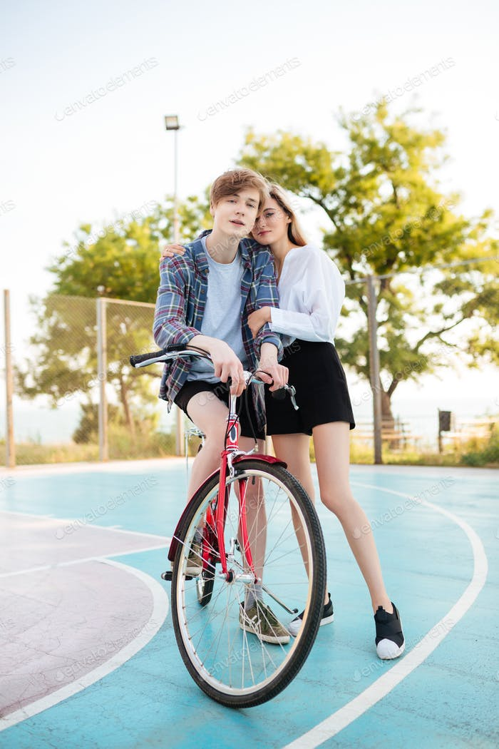 Lovely young couple spending time with bicycle in park