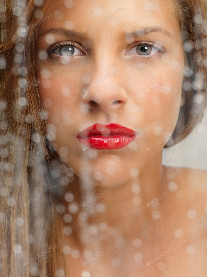 beauty portrait of woman behind wet window