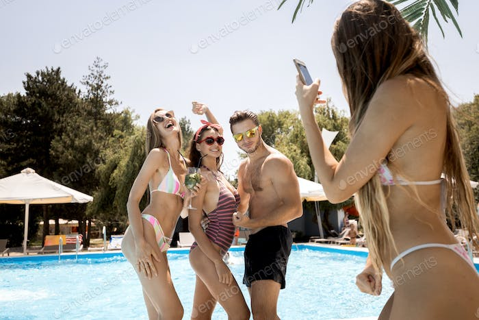 Two stylish young girls in the swimsuits and guy pose for the girl who photographs them next to the
