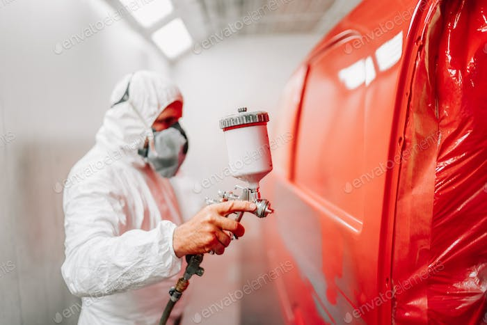 worker painting a car using a paint spray gun