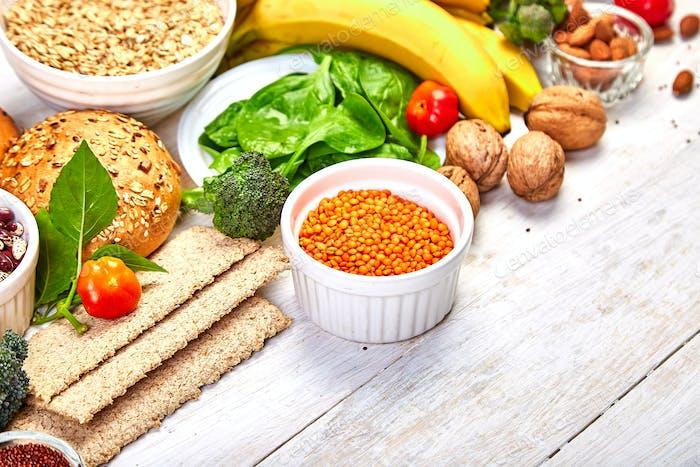 Auswahl Lebensmittel reich an Ballaststoffen auf weißem Holzhintergrund