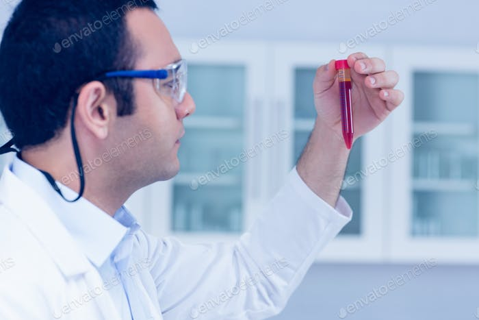 Science student holding up vial at the university