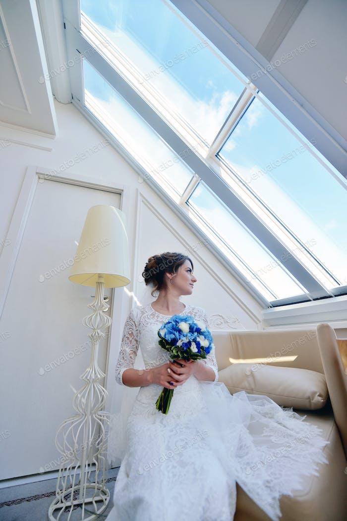 Beauty Braut im Brautkleid mit Blumenstrauß und Spitze Schleier drinnen