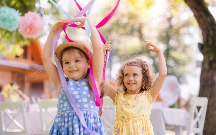 Small girls playing outdoors in garden in summer, birthday celebration concept