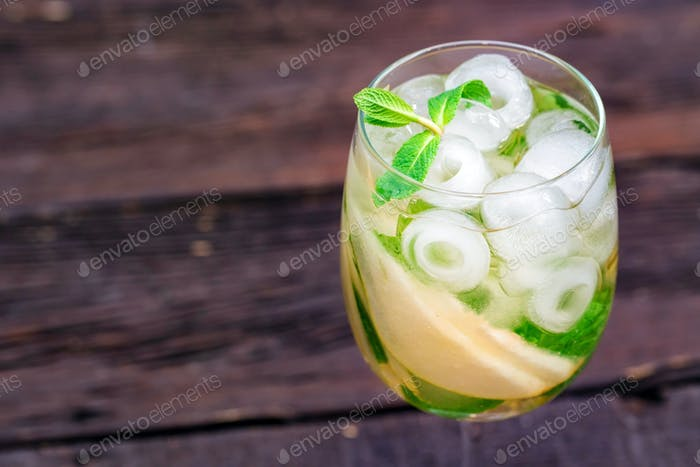 Glass with delicious fresh homemade mojito on wooden background