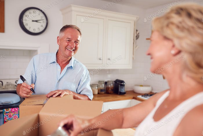 Senior Couple Downsizing In Retirement Packing And Labelling Boxes Ready For Move Into New Home