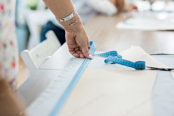Женщина с браслетом измеряет ткань. Мода, портной мастерской