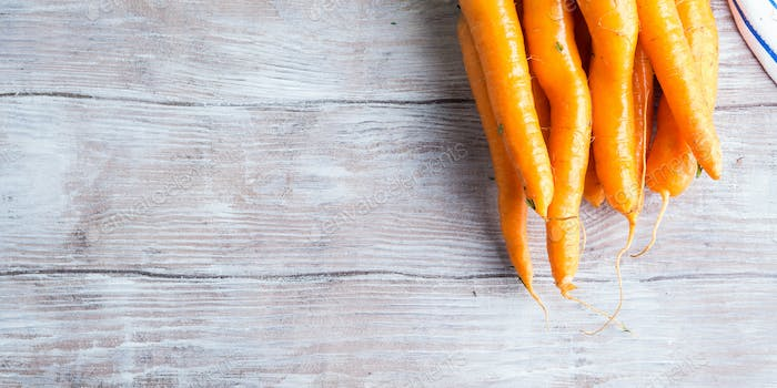Raw carrots on rustic wooden background