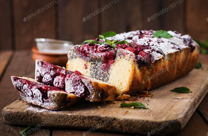 Cherry poppy seed cake dusted with powdered sugar on a wooden table