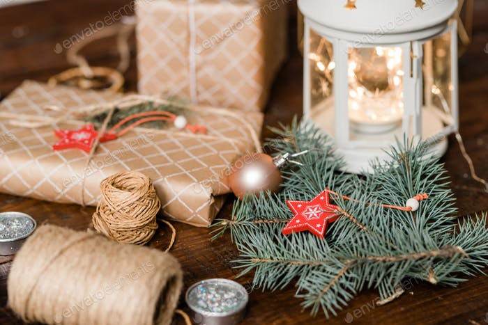 Conifer with star decoration, wrapped giftboxes, threads, candles and lantern