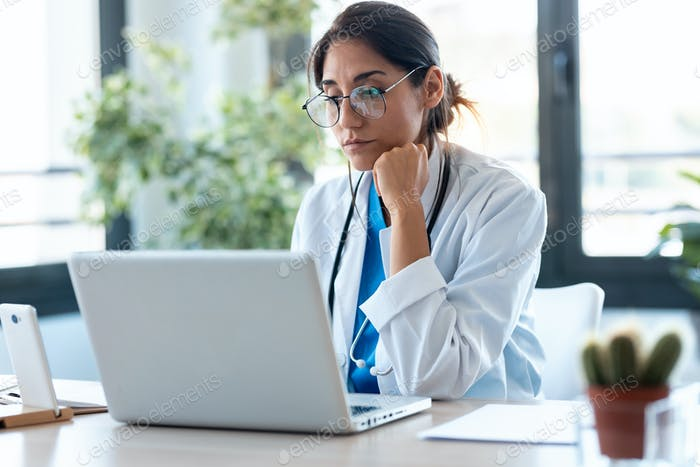 Una doctora seria que trabaja con su computadora portátil en la consulta.