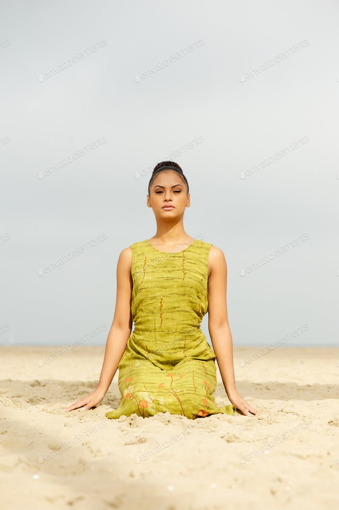 Beautiful woman meditating at the beach