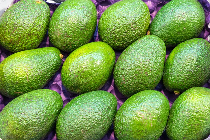 Bunch of ripe green avocados for sale