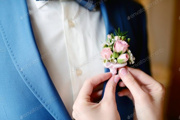 Groom and bride are wearing a boutonniere indoors