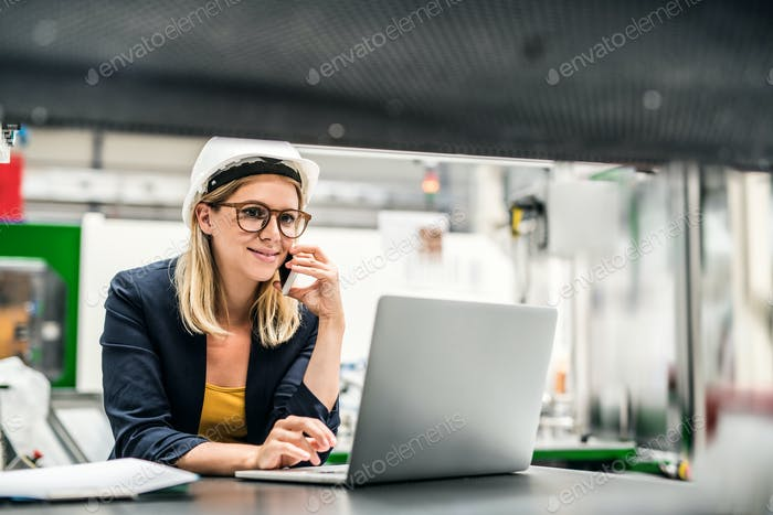 A portrait of an industrial woman engineer in a factory using laptop and smartphone.