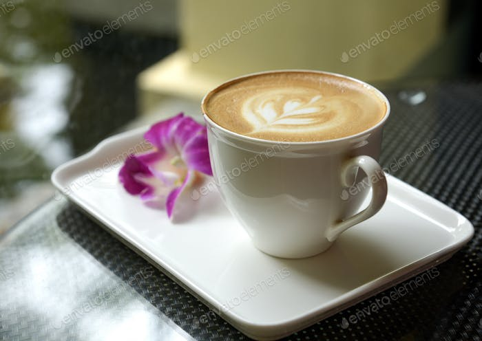 Latte in white mug on ceramic tray with blurred plumeria.