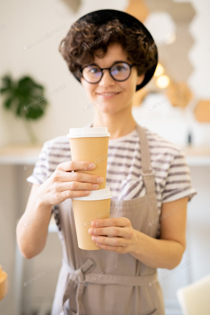 Positive lady in apron brewing tasty coffee in cafe