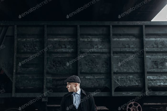 Stylish gangster in retro outfit posing on background of railway