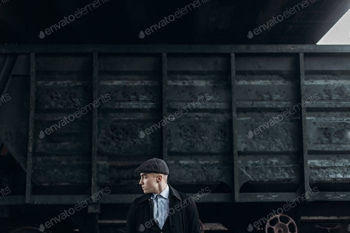 Стильный гангстер в ретро наряд позирует на фоне железной дороги