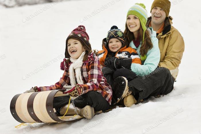 Eine Familie mit zwei Erwachsenen und zwei Kindern, die auf Schlitten im Schnee sitzen.