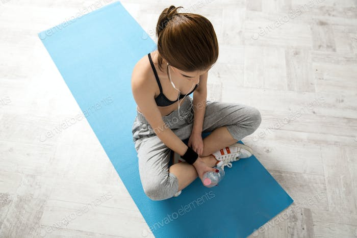 Sporty young woman sitting on the yoga mat at gym