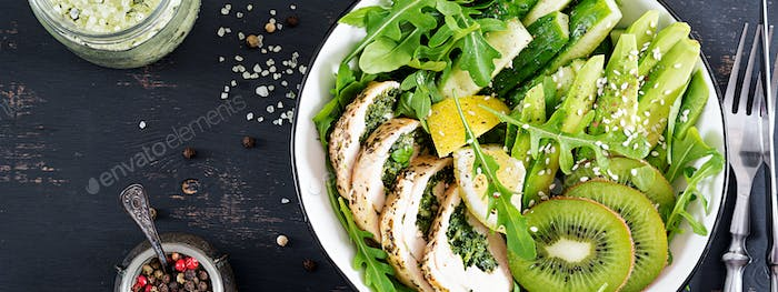 Buddha bowl dish with chicken fillet, avocado, cucumber, fresh arugula salad and sesame.
