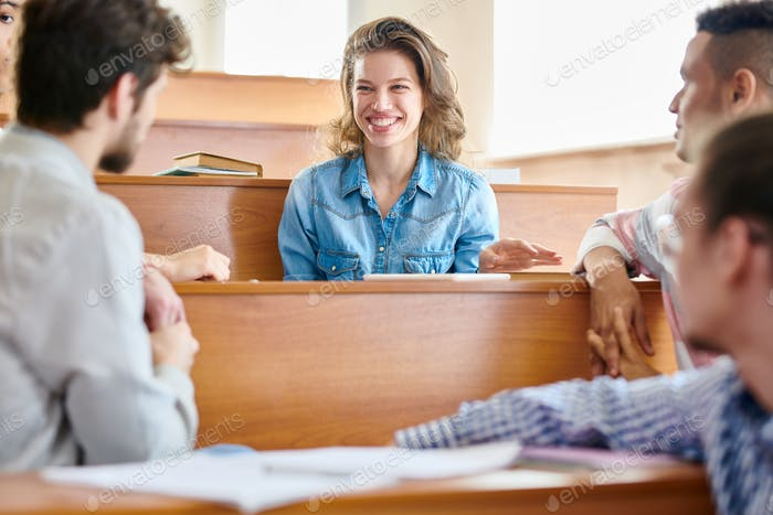 Laughing girl talking to groupmates in lecture room