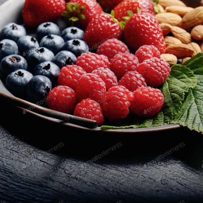 Tray with ripe organic bilberry raspberry strawberry and almonds
