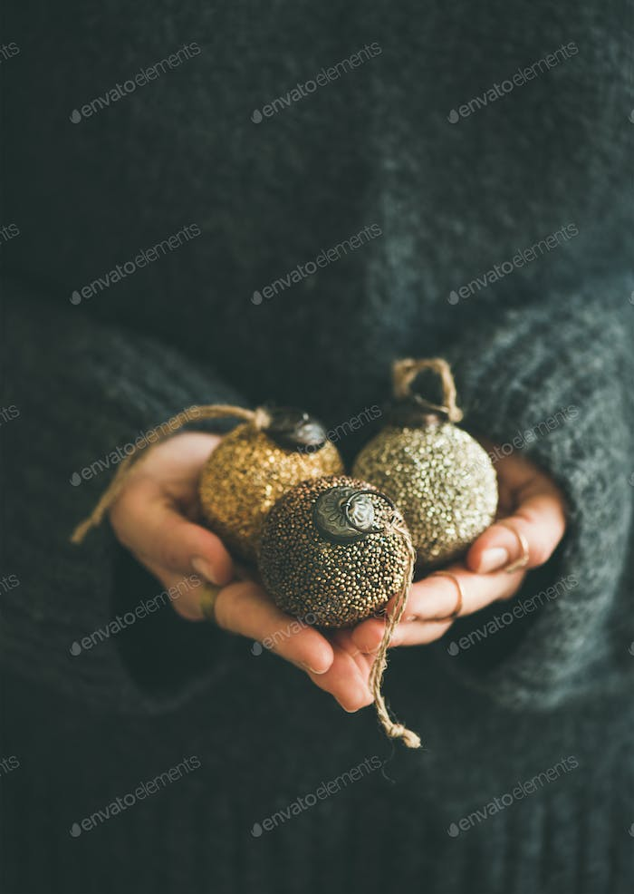 Woman holding golden and silver balls in hands, vertical composition