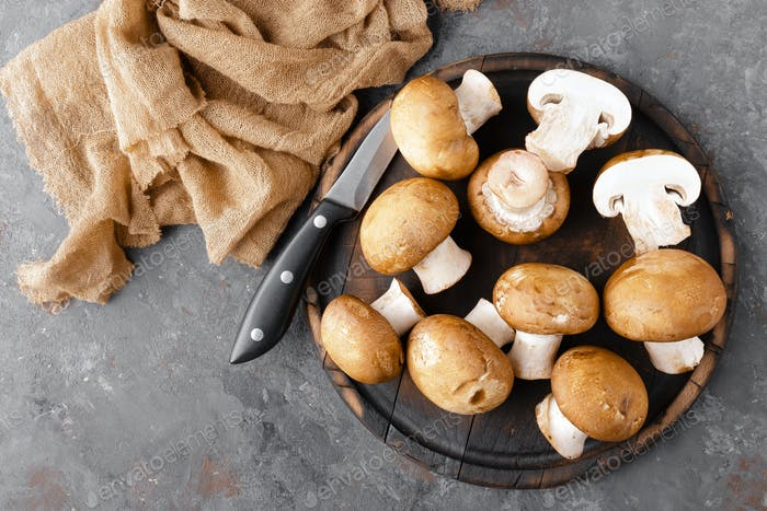 Fresh mushruums on wooden board, top view. Champignon fungi