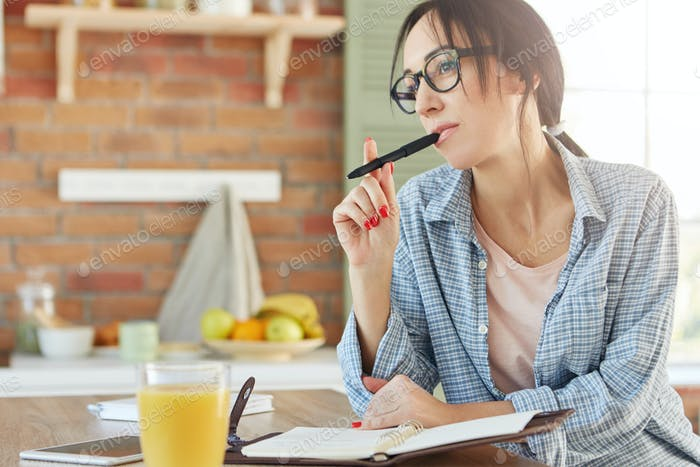 Pensive female model keeps pen, writes recipe in notepad, tries to remember all necessary ingredient