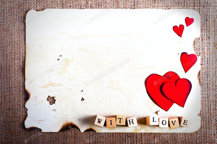 Old vintage sheet of paper, two red hearts, words With love on cubes on burlap, sackcloth background
