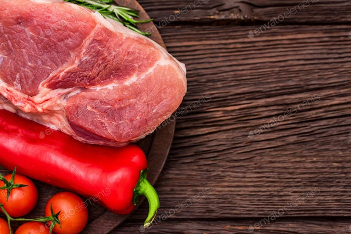Raw pork steak with pepper, herbs and tomatoes