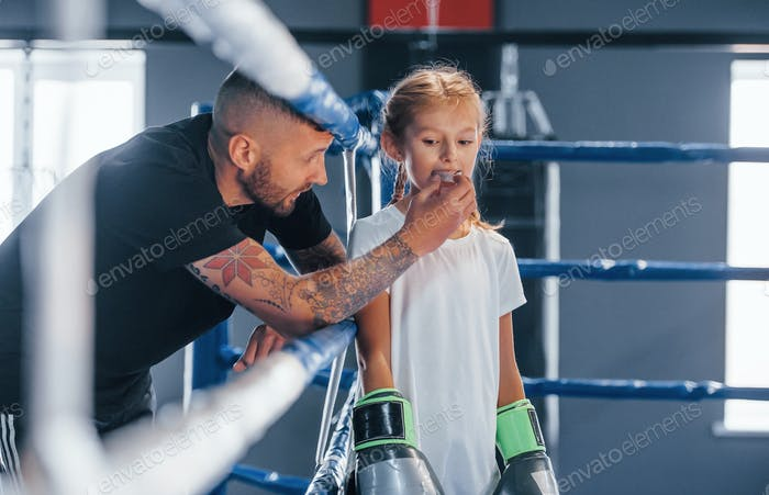 Standing on the boxing ring. Young tattooed boxing coach teaches cute little girl in the gym