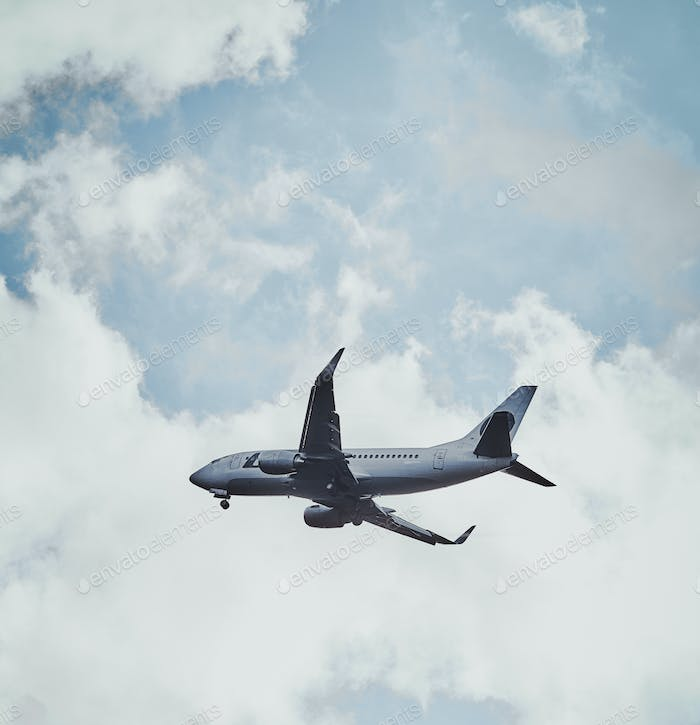 Plane in the cloudy sky is flying from aeroport after rain.