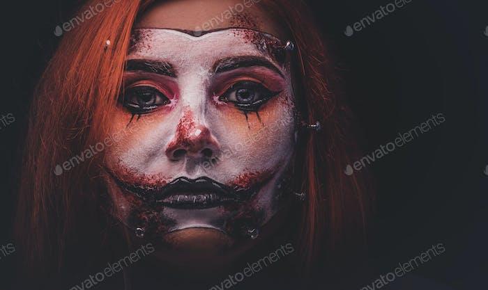 Porträt von Ingwer Mädchen mit beängstigend Puppe Kunst auf Gesicht