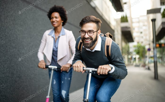 Two smiling business people driving electric scooter going to work