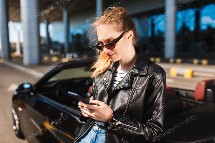 Smiling girl in sunglasses and leather jacket leaning on black c