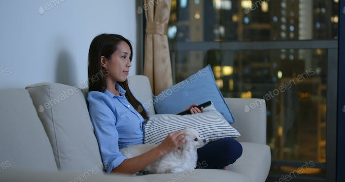Woman watch tv with her pomeranian dog at home