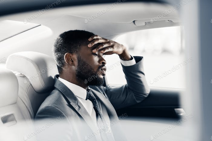 Upset tired businessman sitting in car, thinking about break-up