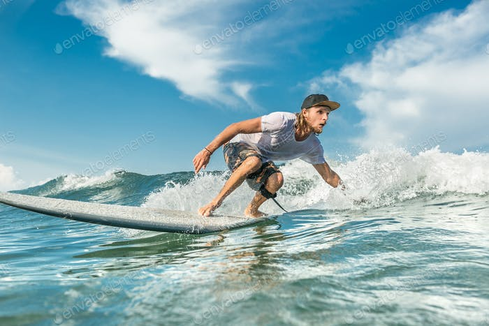 concentrated male surfer riding waves in ocean at Nusa Dua Beach, Bali, Indonesia