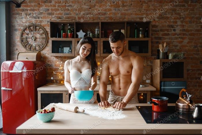 Young couple in underwear cooking on the kitchen